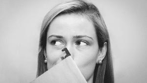 woman hiding behind a folio